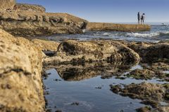 Mature couple walking on the beach with rocks and seaweed. estoril portugal. Europe royalty free stock photos