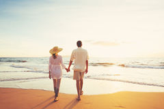 Mature Couple Walking on the Beach at Sunset royalty free stock image