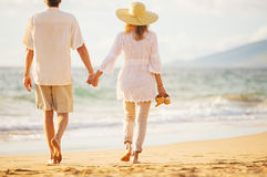 Mature Couple Walking on the Beach at Sunset Royalty Free Stock Images