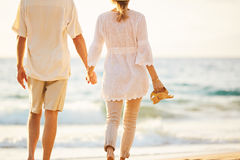 Mature Couple Walking on the Beach at Sunset royalty free stock photography