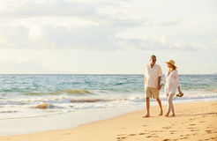 Mature Couple Walking on the Beach at Sunset Stock Photography