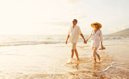 Mature Couple Walking on the Beach at Sunset. Happy Romantic Middle Aged Couple Enjoying Beautiful Sunset Walk on the Beach. Travel Vacation Retirement Lifestyle Royalty Free Stock Photos