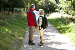 A mature couple walking in the countryside, holding a map Stock Photos