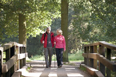 A mature couple walking over a footbridge in the countryside Royalty Free Stock Images