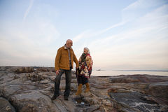 Mature couple walking over rocks Royalty Free Stock Images