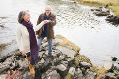 Mature couple walking over rocks Stock Images