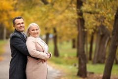 Mature couple walking in park stock images