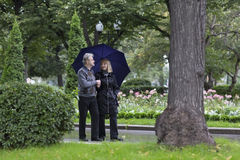 Mature couple walking in a park on a rainy day. Mature couple walking in a park on a rainy autumn day stock photos