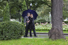 Mature couple walking in a park on a rainy day Royalty Free Stock Photo