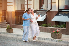 Mature couple walking and smiling. Royalty Free Stock Image