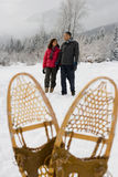 Mature couple walking through snow Royalty Free Stock Image
