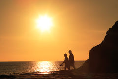 Mature couple walking in sunset. Silhouette of aged couple walking at the beach in sunset Stock Photos