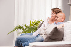 Mature couple watching tv on the sofa Royalty Free Stock Photos