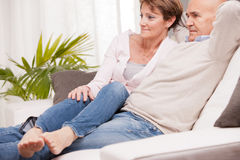 Mature couple watching tv on the sofa Royalty Free Stock Images