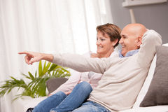 Mature couple watching tv on the sofa Royalty Free Stock Photo