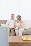 Mature couple watching tv in their living room Stock Images