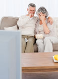 Mature couple watching tv in their living room Royalty Free Stock Image