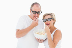 Mature couple wearing 3d glasses eating popcorn Royalty Free Stock Photography
