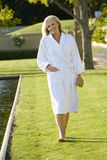 Mature couple wearing white bath robe walking by swimming pool, smiling, portrait Royalty Free Stock Image