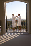 Mature couple wearing white bath robes, standing on balcony with drinks, view through doorway Stock Photo