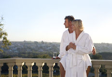 Mature couple wearing white bath robes, standing on balcony, embracing Royalty Free Stock Images