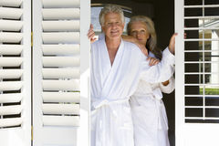 Mature couple wearing white bath robes, standing in doorway, smiling, portrait Stock Image