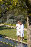 Mature couple wearing white bath robes, standing on lawn together, elevated view Royalty Free Stock Images