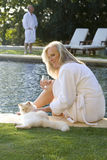 Mature couple wearing white bath robes by swimming pool, woman smiling at cat in foreground Royalty Free Stock Photo