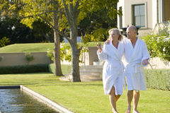 Mature couple wearing white bath robes walking by swimming pool, smiling Stock Photography