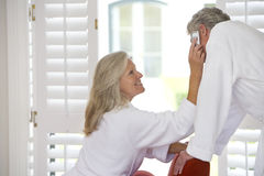 Mature couple wearing white bath robes, woman holding mobile phone to man's ear Stock Images