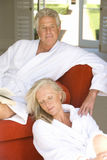 Mature couple wearing white bath robes, woman sitting on floor by man with book on sofa Royalty Free Stock Photos