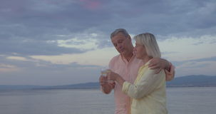 Mature Couple with Wine Glasses Walking by the Sea. Steadicam shot of mature couple walking by the sea at sunset with wine glasses in hands stock video