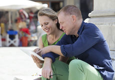 Mature couple working on laptop outdoors Royalty Free Stock Photos