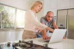 Mature couple working together on a laptop at home Royalty Free Stock Photography