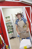 Mature cowboy pushing cart with sack in feed store Stock Photography
