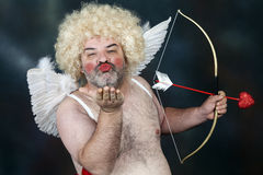 Mature Cupid. Fat bearded mature hairy cupid with bow and heart arrow. Sending a kiss stock photography