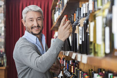 Mature Customer Choosing Wine Bottle In Store. Portrait of smiling mature customer choosing wine bottle in store Stock Images