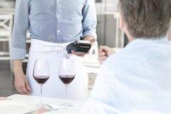 Mature customer paying through credit card at restaurant stock image