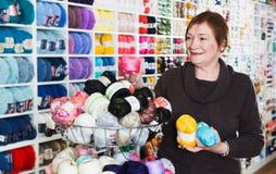 Mature customer in yarn shop. Smiling mature woman choosing yarn among diversity on shelves in needlework store Royalty Free Stock Image