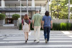Mature dad and children: boy and girl are walking in the street in the back. Concept of family, paternity. Mature dad and children: boy and girl are walking away royalty free stock photo