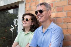 Mature dad and teenager son wearing sunglasses and looking away. Fathers Day. Concept of family, relationship, different. Mature dad and teenager son wearing stock photo