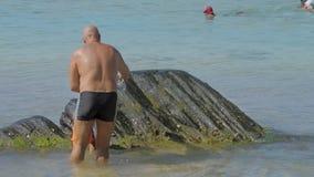 Daddy helps son climb on wet rocks in clear ocean water