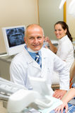 Mature dental surgeon in office with assistant Stock Photos