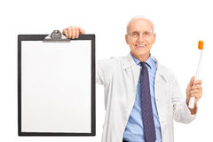 Mature dentist holding a toothbrush and a clipboard Royalty Free Stock Photo