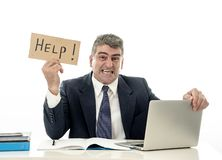 Mature desperate businessman suffering stress working at computer desk holding sign asking for help looking stressed overworked. And helpless isolated in white stock photography