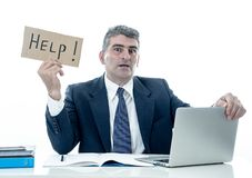 Mature desperate businessman suffering stress working at computer desk holding sign asking for help looking stressed overworked. And helpless isolated in white royalty free stock photography