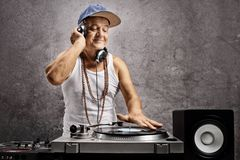 Mature dj with headphones playing music at a turntable. Against a grey wall stock image