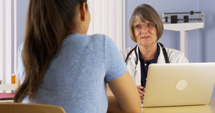 Mature doctor advising Mexican woman patient Stock Photos