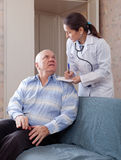 Mature doctor asks senior man feels Royalty Free Stock Photos