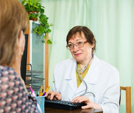 Mature  doctor assist female patient Royalty Free Stock Image